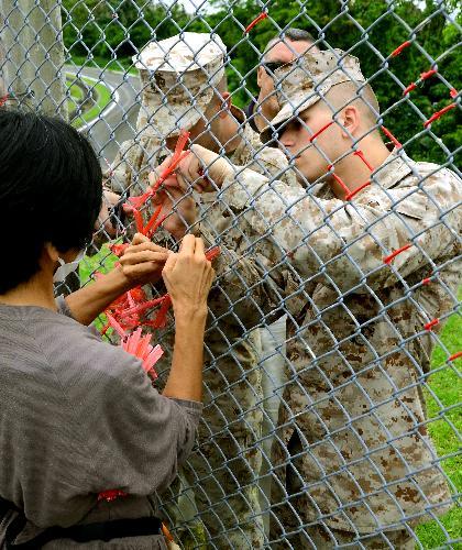 基地に貼られた赤いテープを撤去する米軍兵士とボランティア